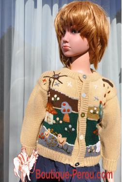 Veste enfant de couleur crème avec des motifs fait main.